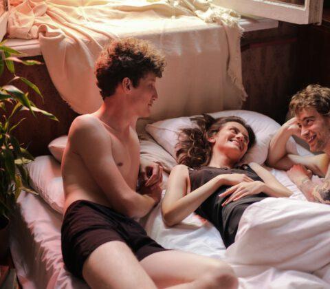 dwóch mężczyzn i kobieta w łóżku